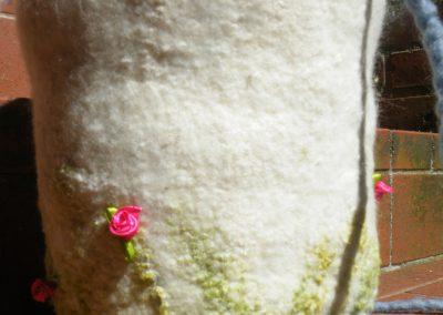 Rückseite, kleine schmückende Röschen und zarte Seide in frühlingshaftes grün. Die Urne ist komplett umschlossen und von der Form her einfach und schlicht.