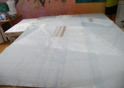 1. Schritt: nach dem Maßnehmen wird auf die zugeschnittene Schablone die Chiffonseide paßgenau mit Randzugabe gelegt. Die Schablone ist bei dieser Technik etwa 50% größer als der fertige Mantel.